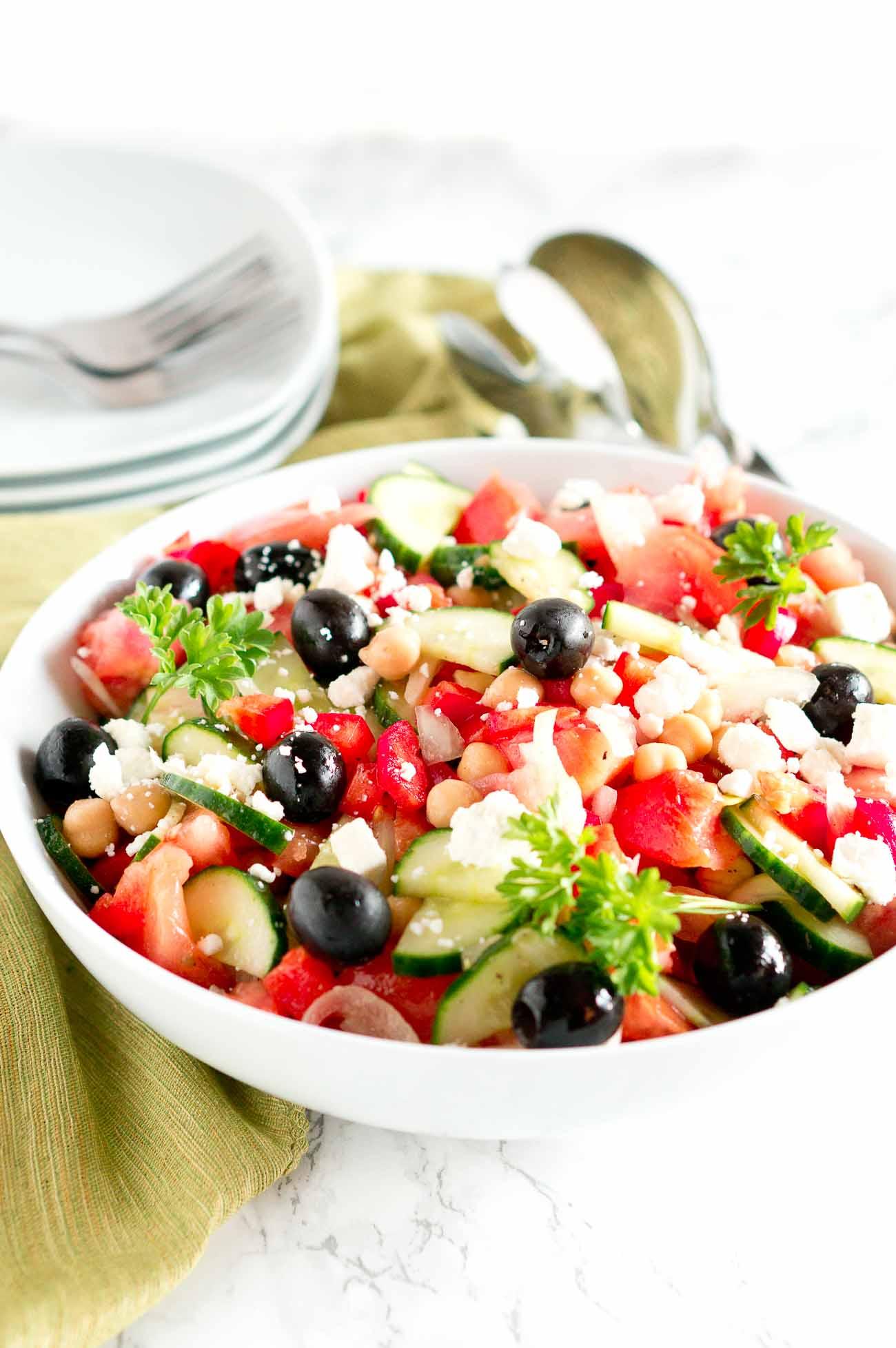 Greek Salad (aka Mediterranean salad) in a white bowl with green towel