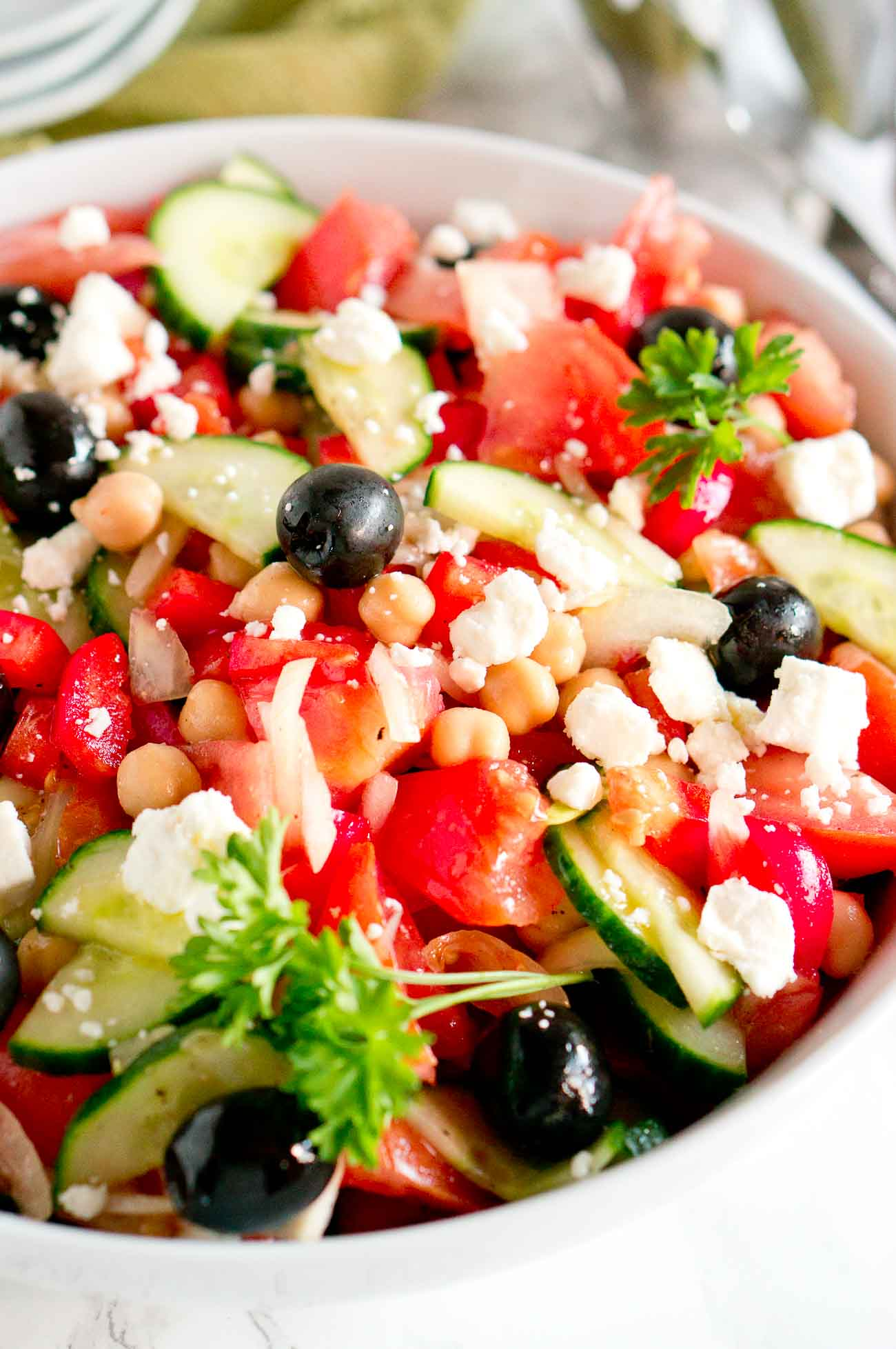 close up shot of tomatoes, cucumbers, peppers, olives and other ingredients in a Greek salad