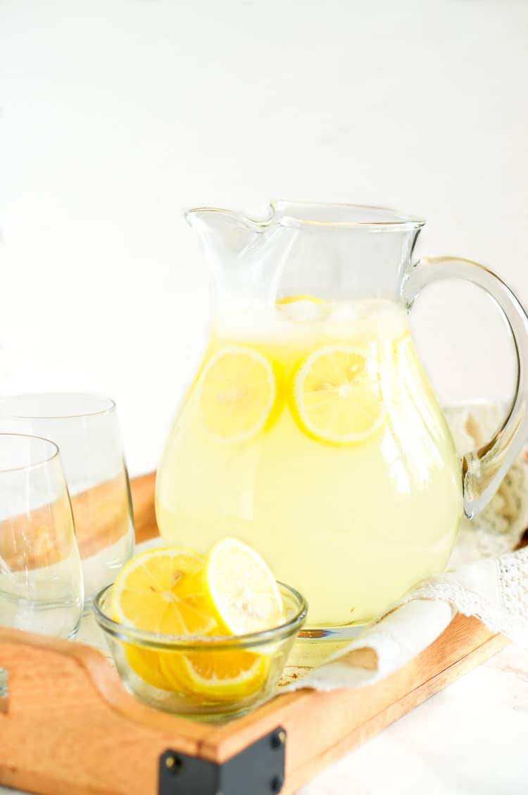 homemade lemonade in a glass pitcher with lemons