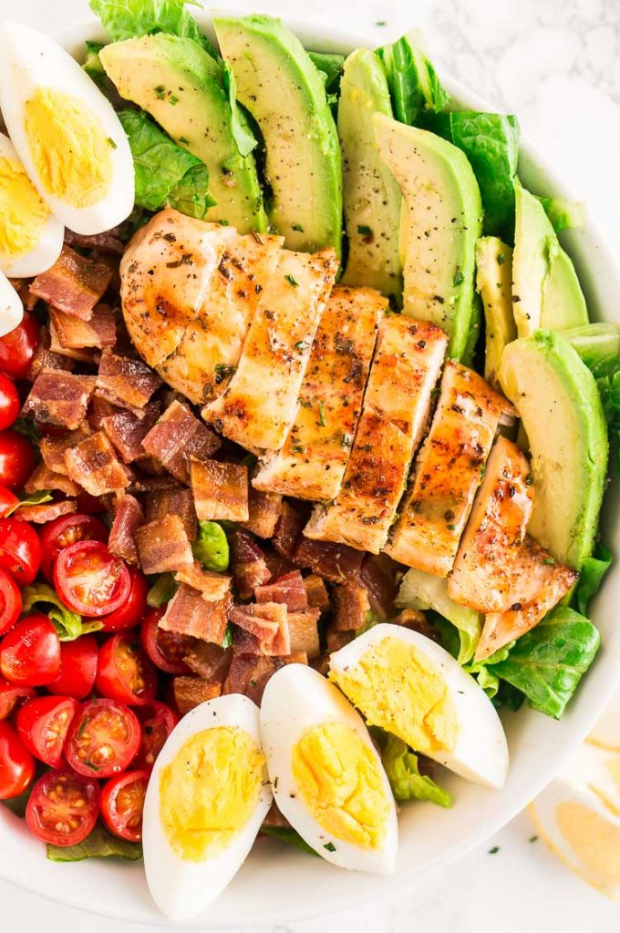 close up image of chicken cobb salad served in a large bowl