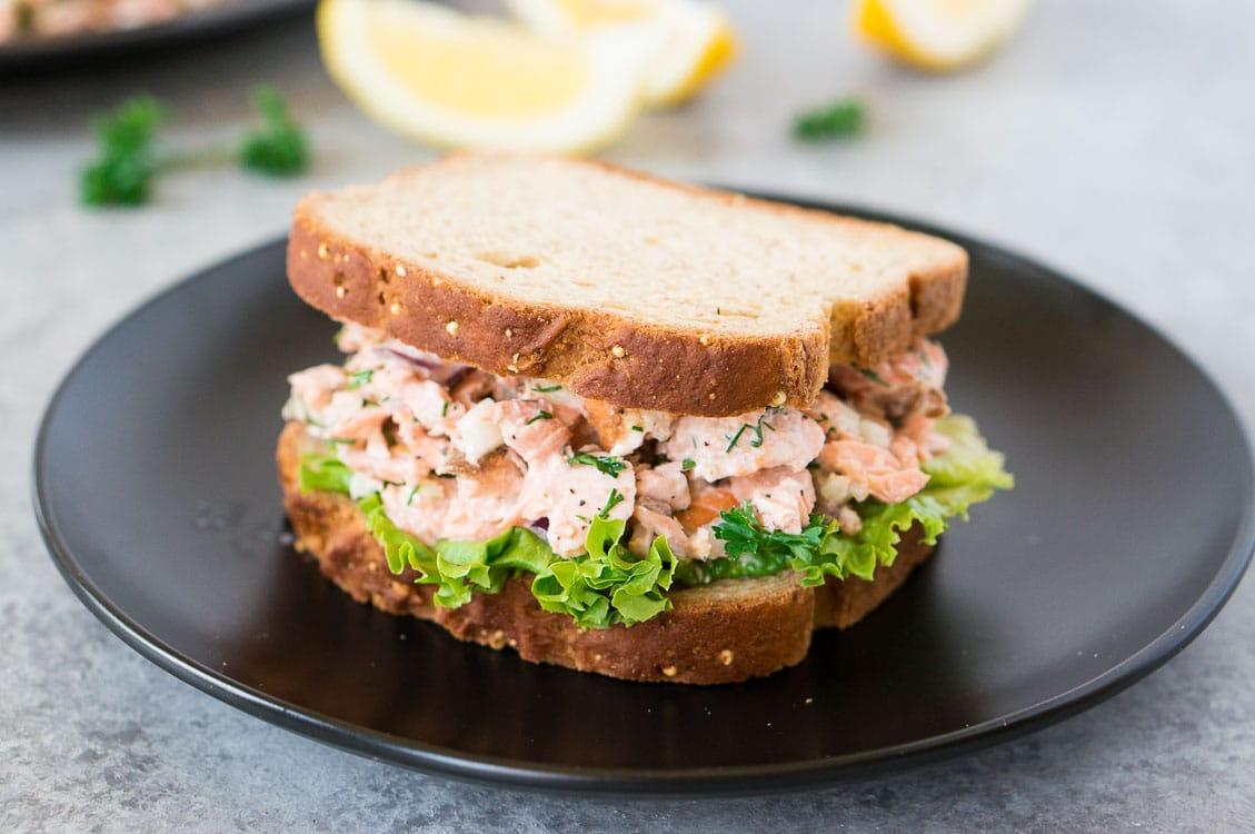 salmon salad sandwich on a black plate