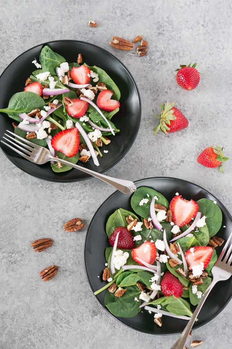 strawberry spinach salad recipe on a black plate with a fork