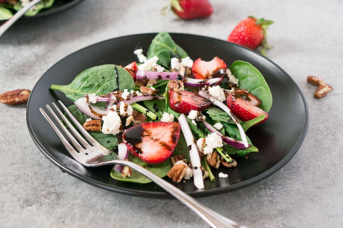 spinach and strawberry salad in a black plate