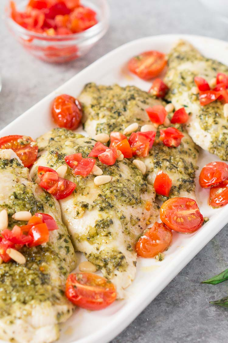 close up shot of basil pesto chicken on a white plate
