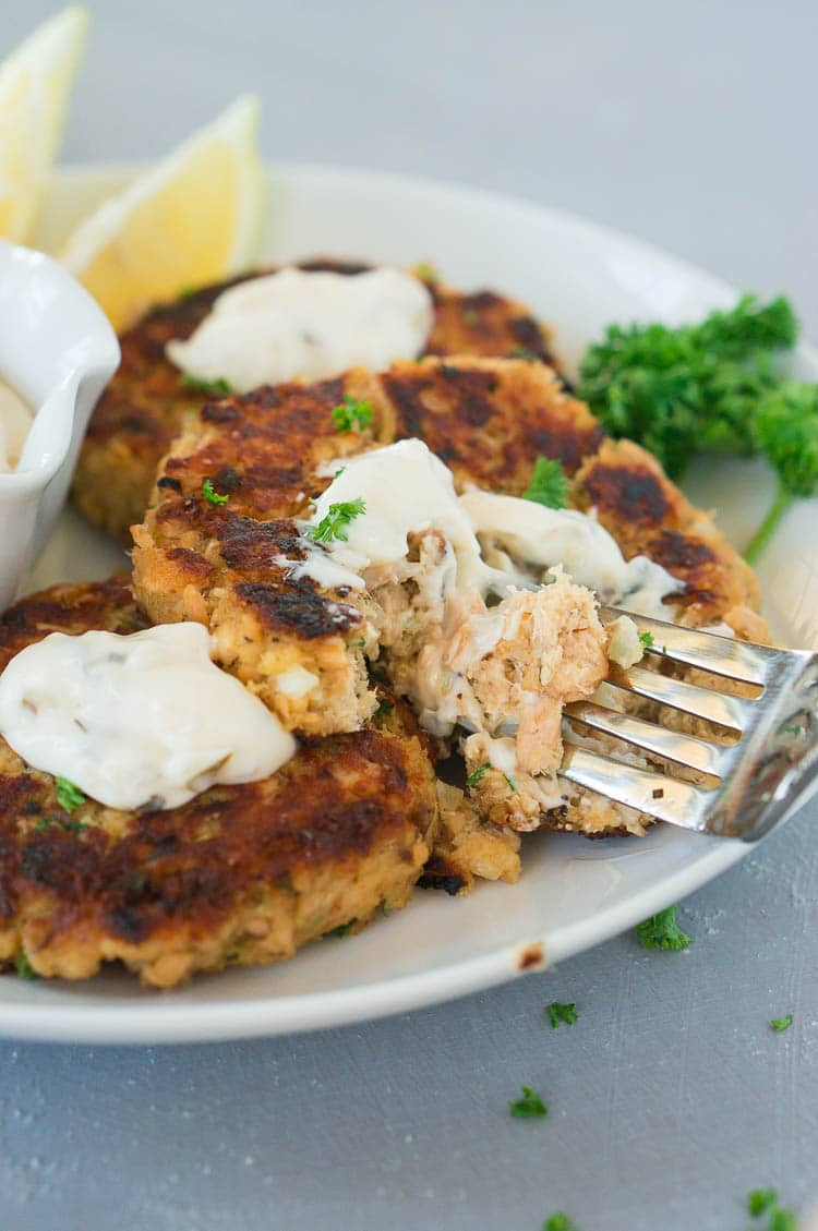 taking a bite with a fork from salmon fish cakes