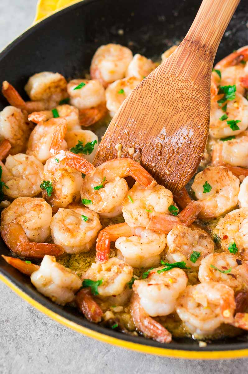 easy shrimp scampi recipe in a skillet with a wooden spoon