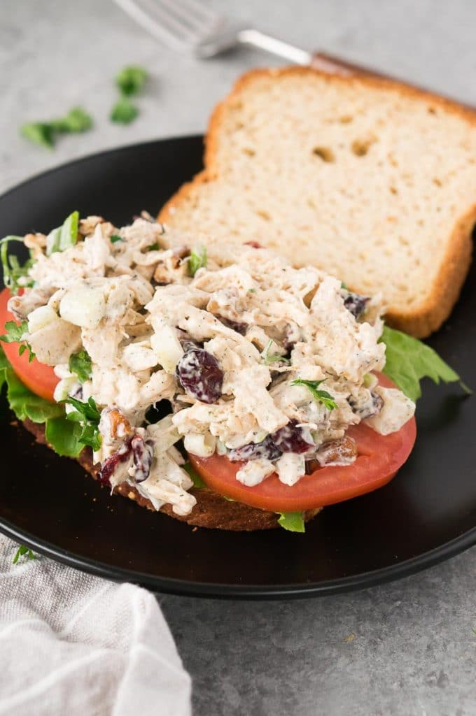 old fashioned turkey salad sandwich on a black plate