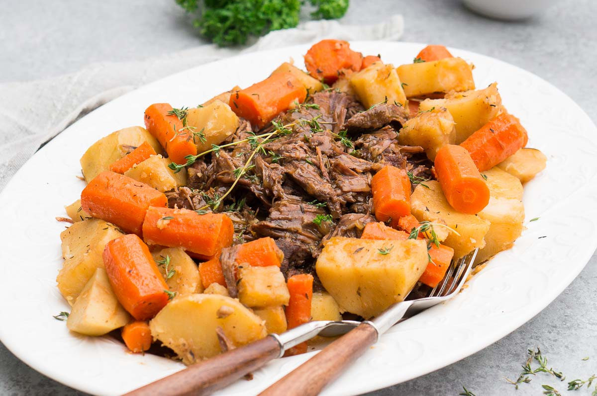 beef roast in instant pot served with potatoes and carrots on a white plate