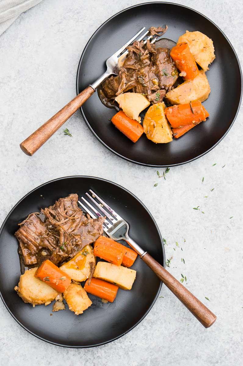 pressure cooker roast with vegetables served in black plates