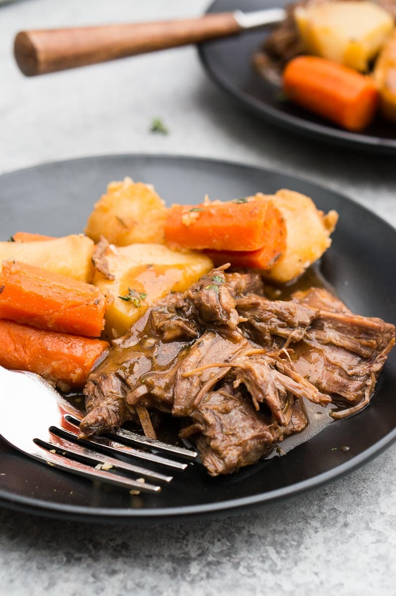 pressure cooker pot roast served on a black plate with a fork