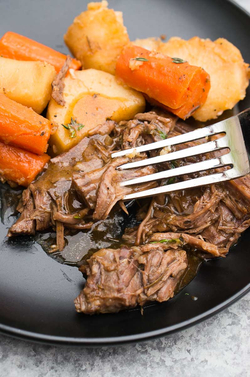 close up of pressure cooker beef roast with potatoes and carrots on a plate
