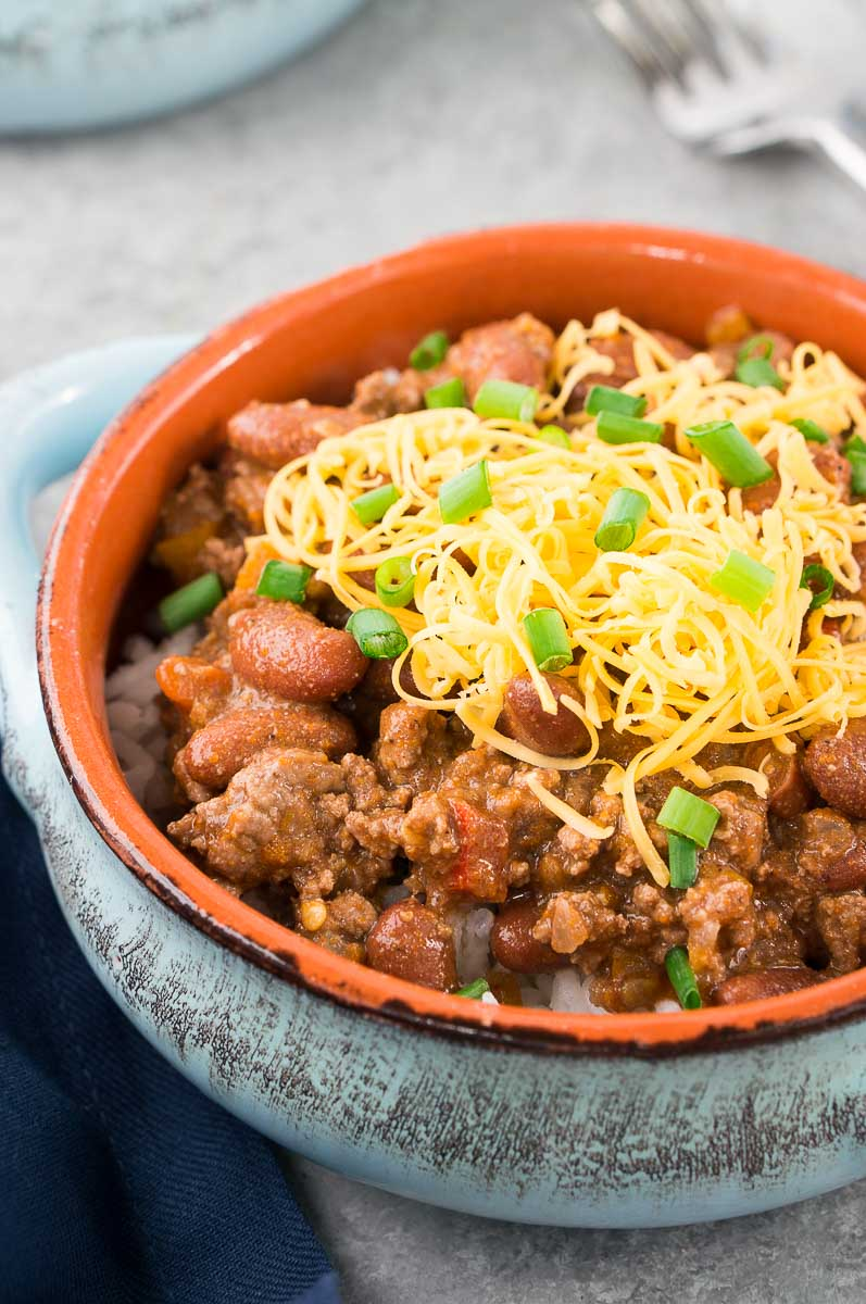 close up of chili recipe with shredded cheese and onions