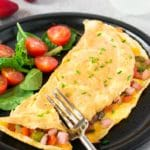 western omelet with greens and cherry tomatoes on a plate