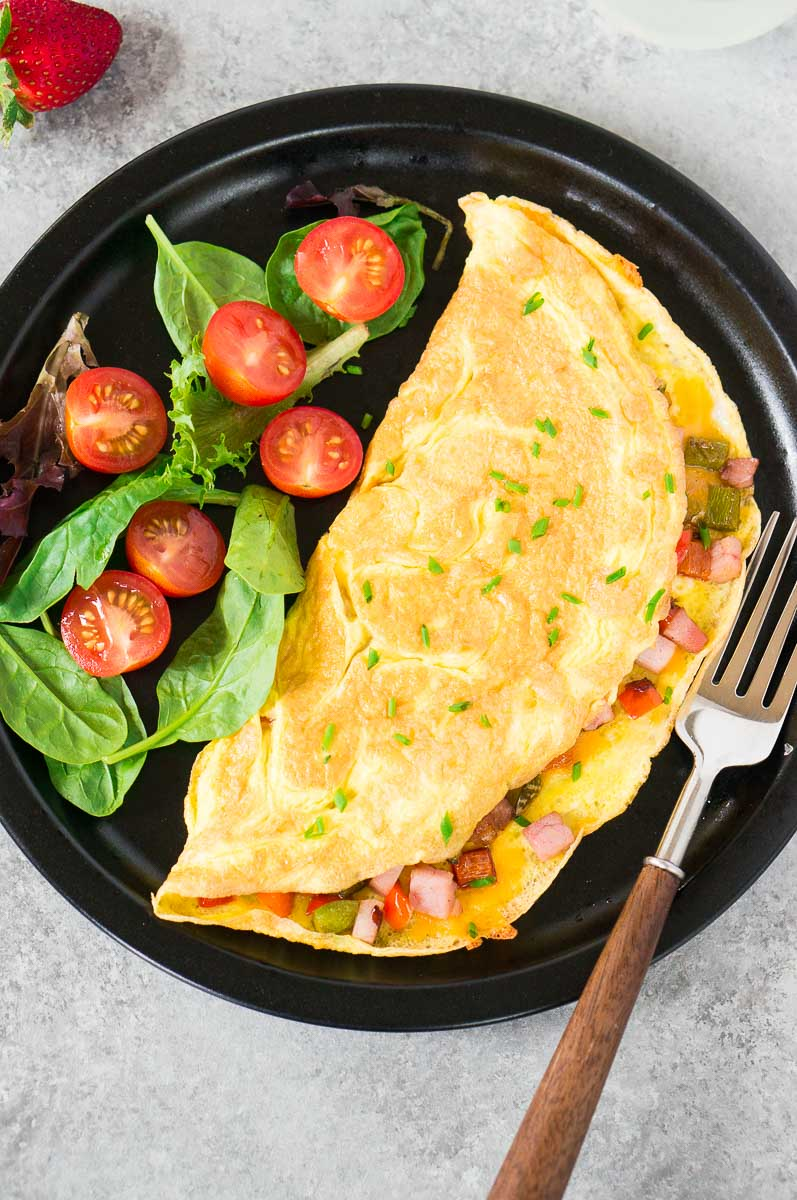 omelet for breakfast & greens on a black plate