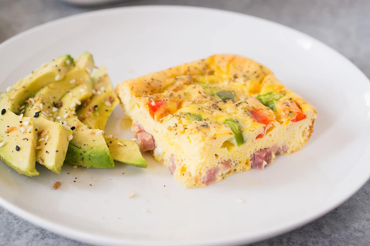 slice of breakfast casserole and sliced avocado on a plate