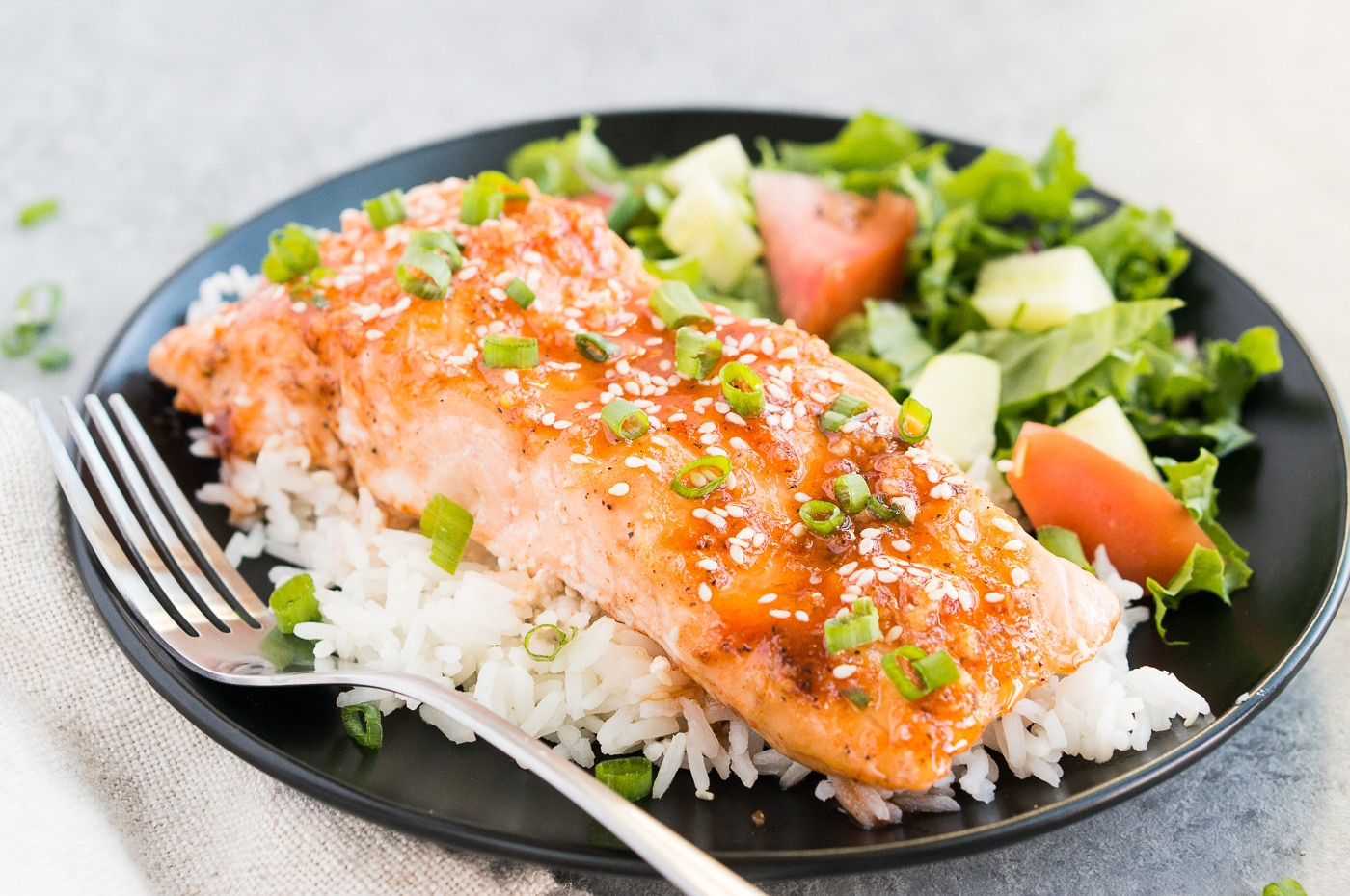 honey glazed salmon over rice with salad on a black plate