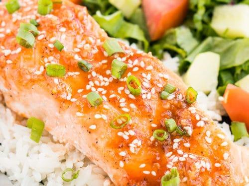 close up of honey sriracha glazed salmon over rice