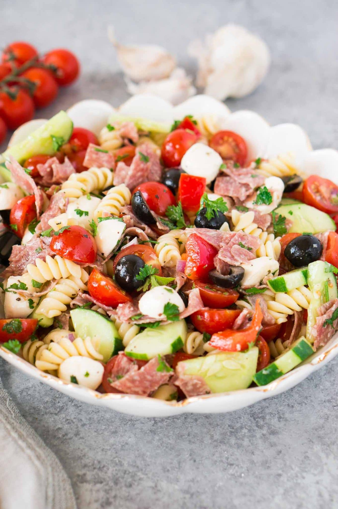 Pasta salad with mozzarella salami tomatoes and cucumbers in a bowl