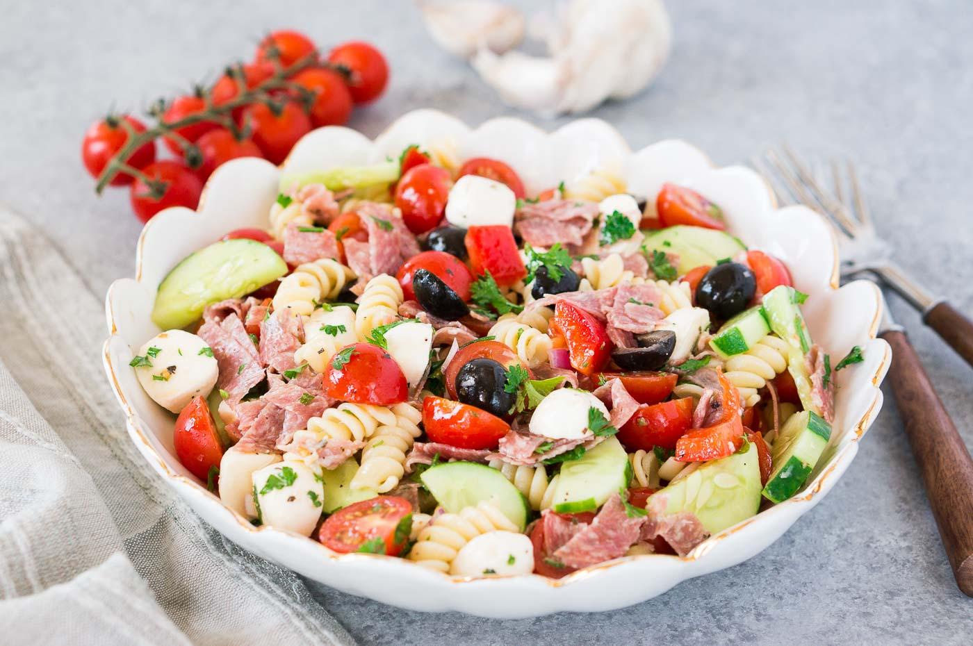 homemade pasta salad with tomatoes cucumbers salami and mozzarella