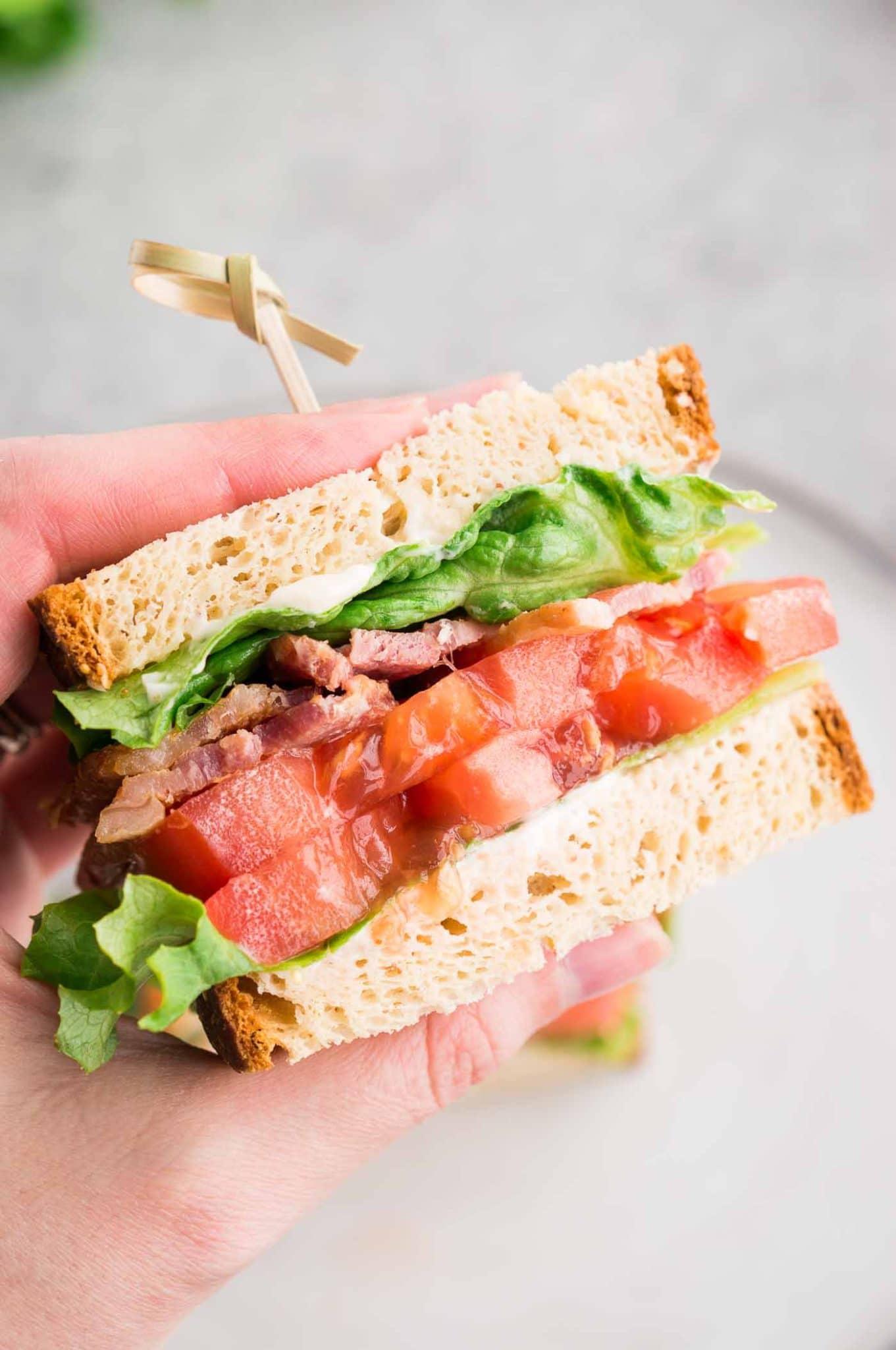 holding sliced tomato bacon sandwich