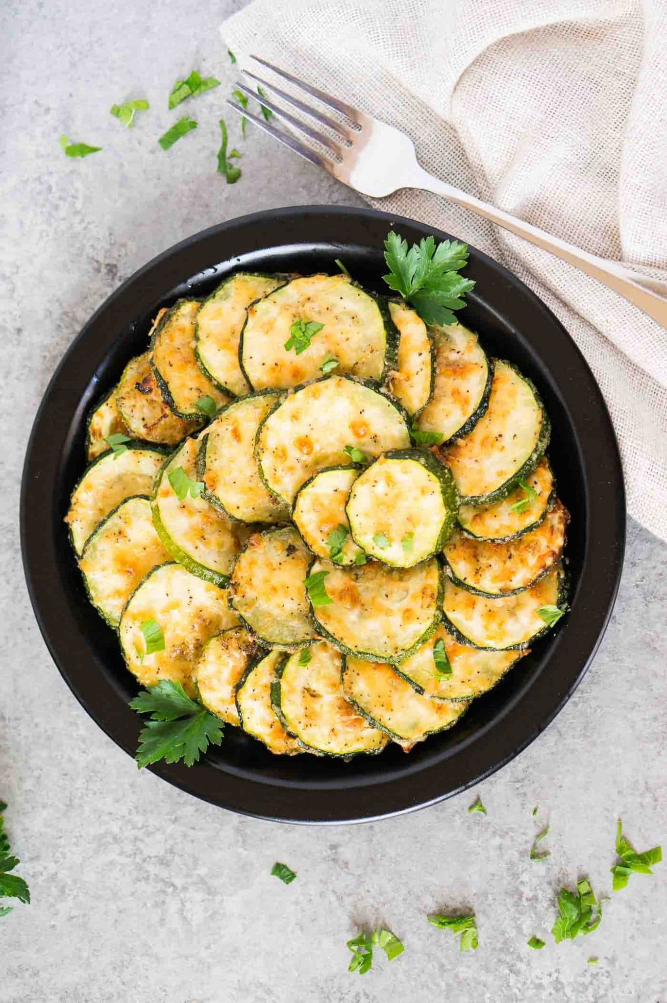 roasted zucchini slices on a black plate