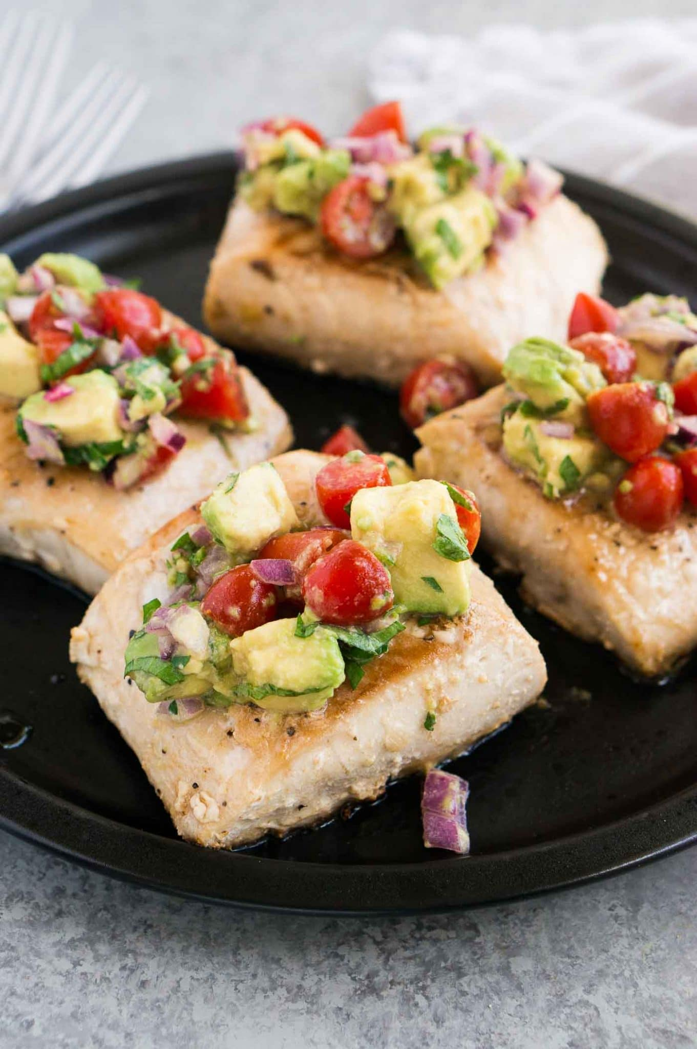 pan seared white fish with avocado salsa on a plate