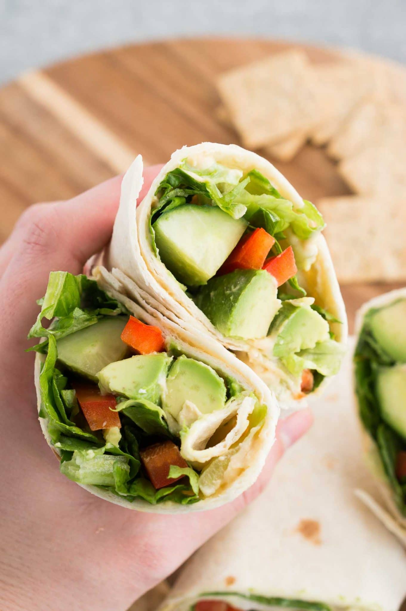 holding a vegan wrap sliced in half